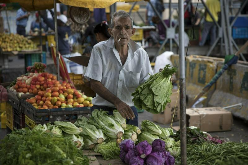 A vendor arranges his produce at the Quinta Crespo street market in downtown Caracas, Venezuela, Saturday, Jan. 26, 2019. The country's political showdown moves to the United Nations Saturday where a Security Council meeting called by the United States will pit backers of President Nicolas Maduro against the Trump administration and supporters of the country's self-declared interim leader Juan Guaido. (AP Photo/Rodrigo Abd)