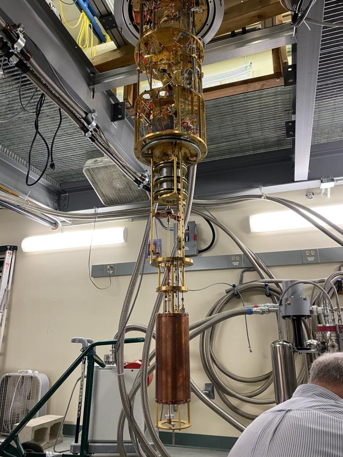 The HAYSTAC detector, a large copper cylinder connected to a gold-plated assembly of tubes and wires hanging from the ceiling of a lab.