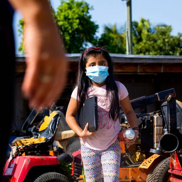 A young migrant girl walks toward a Miami-Dade County Public Schools employee who had taken a lead role on assisting the kids with virtual learning during the coronavirus pandemic in South Florida on Thursday, May 21, 2020.