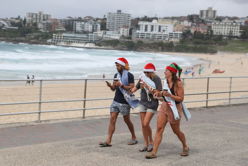 People wear Santa hats on Christmas Day at Bondi Beach in Sydney