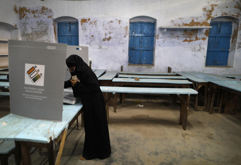 An Indian Muslim woman casts her vote inside a polling station in Varanasi, India, Sunday, May 19, 2019. Indians are voting in the seventh and final phase of national elections, wrapping up a 6-week-long long, grueling campaign season with Prime Minister Narendra Modi's Hindu nationalist party seeking reelection for another five years. Counting of votes is scheduled for May 23. (AP Photo/Rajesh Kumar Singh)