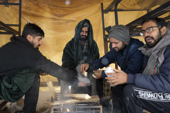 Migrants eat, at the Lipa camp, outside Bihac, Bosnia, Monday, Jan. 11, 2021. Aid workers say migrants staying at a camp in northwestern Bosnia have complained or respiratory and skin diseases after spending days in make-shift tents and containers amid freezing weather and snow blizzards. Most of the hundreds of migrants at the Lipa facility near Bosnia's border with Croatia on Monday have been accommodated in heated military tents following days of uncertainty after a fire gutted most of the camp on Dec. 23. (AP Photo/Kemal Softic)
