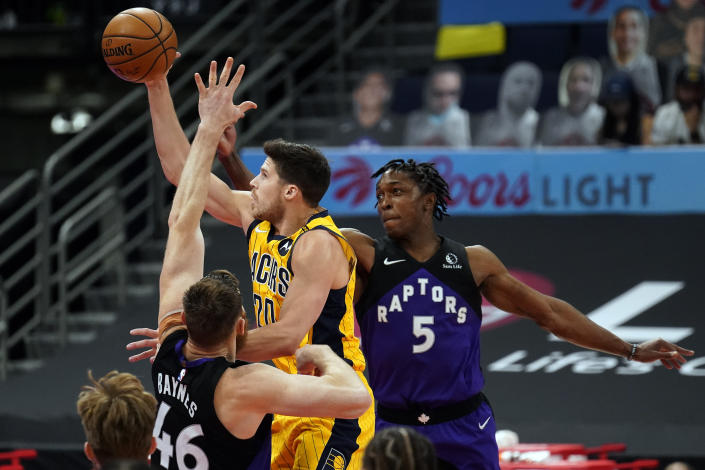 Indiana Pacers forward Doug McDermott (20) puts up a shot between Toronto Raptors center Aron Baynes (46) and forward Stanley Johnson (5) during the second half of an NBA basketball game Sunday, May 16, 2021, in Tampa, Fla. (AP Photo/Chris O'Meara)