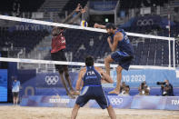 Daniele Lupo, right, of Italy, takes a shot as teammate Paolo Nicolai, center watches and Ahmed Tijan, of Qatar, defends during a men's beach volleyball quarterfinal match at the 2020 Summer Olympics, Wednesday, Aug. 4, 2021, in Tokyo, Japan. (AP Photo/Petros Giannakouris)