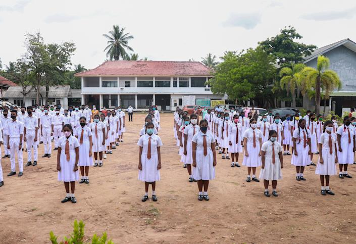 Students attending morning assemblies wear face masks after their schools were reopened in Panadura, Sri Lanka, on July 6. The government announced all schools would reopen for students in grades 5, 11 and 13 after they were closed in March due to the coronavirus pandemic.
