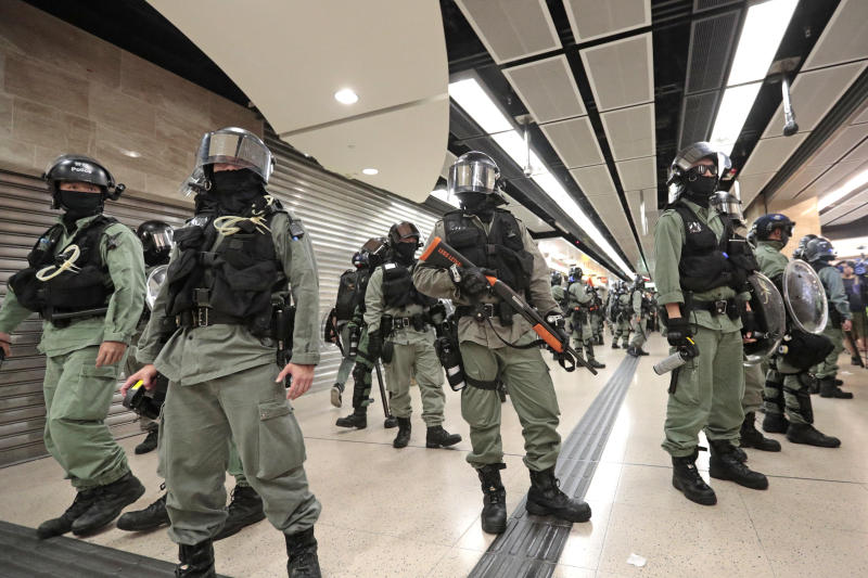 Riot police form a line at a shopping mall in Hong Kong, Sunday, Nov. 3, 2019. Riot police stormed several malls in Hong Kong on Sunday in a move to thwart more pro-democracy protests, as the city's leader heads to Beijing for talks on deepening economic integration between the semi-autonomous Chinese territory and mainland China. (AP Photo/Dita Alangkara)