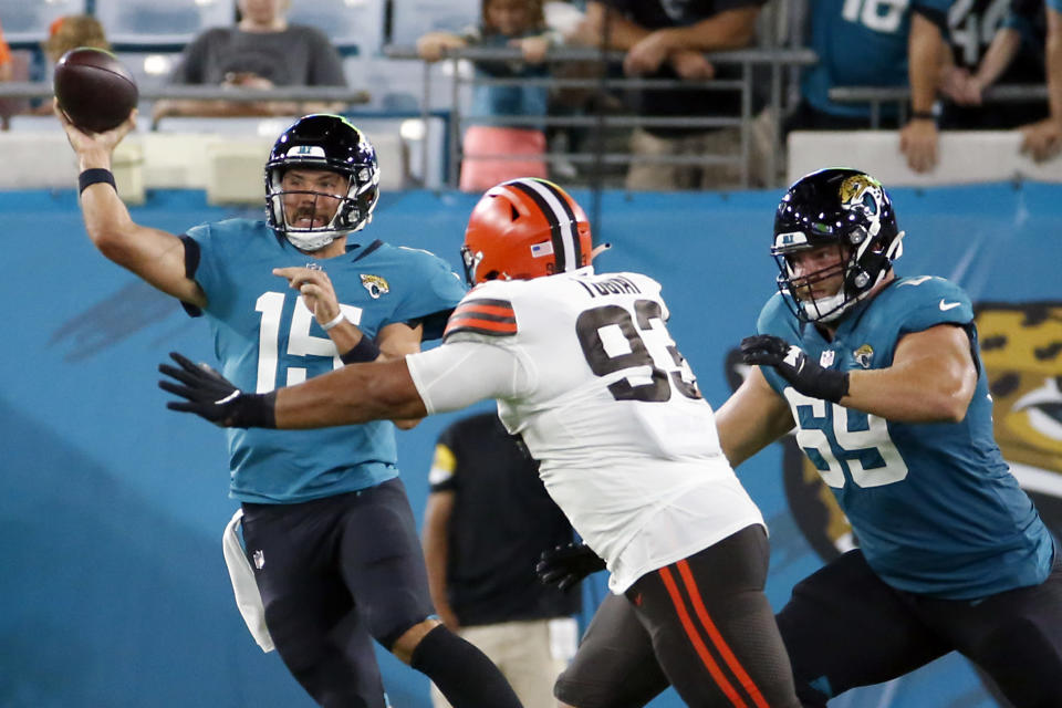 Jacksonville Jaguars quarterback Gardner Minshew (15) throws a pass as he is pressured by Cleveland Browns defensive tackle Tommy Togiai (93) during the first half of an NFL preseason football game, Saturday, Aug. 14, 2021, in Jacksonville, Fla. (AP Photo/Stephen B. Morton)