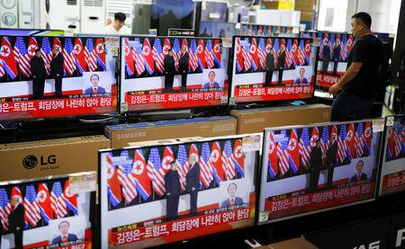 A shopkeeper walks past a set of TV's broadcasting a news report on summit between the U.S. and North Korea, in Seoul, South Korea, June 12, 2018.   REUTERS/Kim Hong-Ji/Files