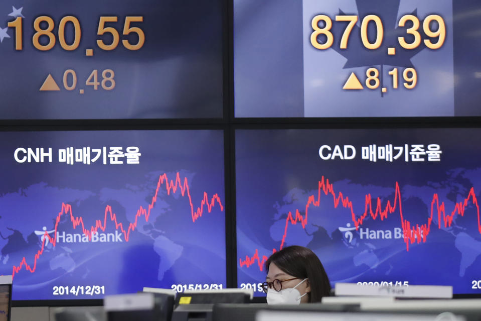 A currency trader watches computer monitors near the screens showing the foreign exchange rates at the foreign exchange dealing room in Seoul, South Korea, Friday, Jan. 15, 2021. Asian shares were mixed on Friday after a late slide in several Big Tech stocks left major indexes lower on Wall Street. (AP Photo/Lee Jin-man)