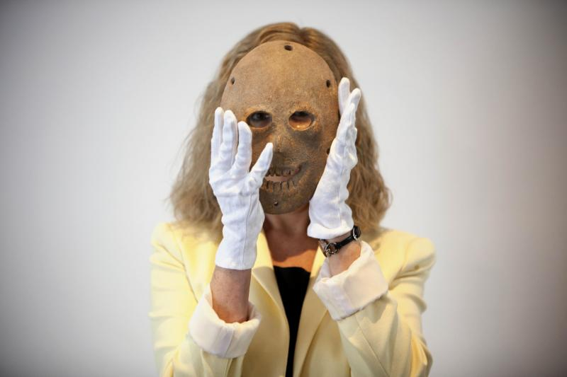 Curator Debby Hershman holds a 9,000 year old Neolithic stone mask during the launch of Google Art project at the Israel Museum in Jerusalem, Tuesday, April 3, 2012. Israel's national museum announced Tuesday it is joining the Google Art project, which provides online tours of museums around the world.(AP Photo/Oded Balilty)