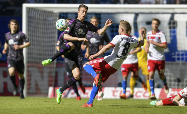 Freiburg's Janik Haberer, left, tries to defend, while Hamburg's Lewis Holtby kicks the ball, front, during the German Bundesliga soccer match between Hamburger SV and SC Freiburg, in Hamburg, Germany, Saturday, April 21, 2018. (Axel Heimken/dpa via AP)