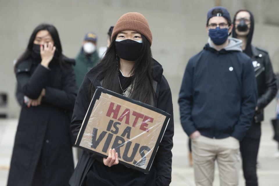 A woman holds a sign reading Hate is a Virus at a rally.