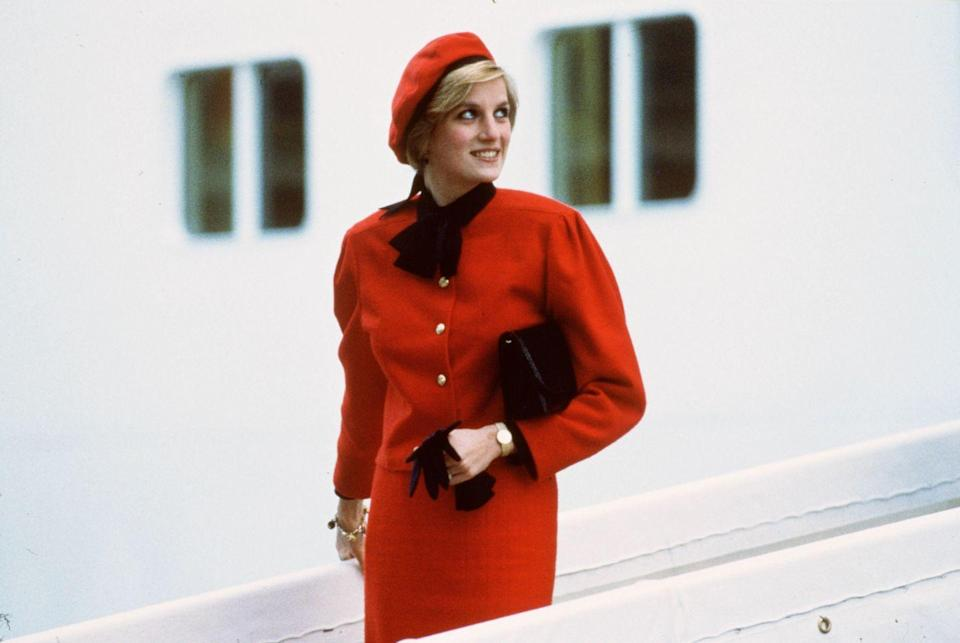 """<p>In a red skirt-suit with gold button, matching beret, and a gold charm bracelet at the naming ceremony for the P&O cruise liner """"Royal Princess.""""</p>"""