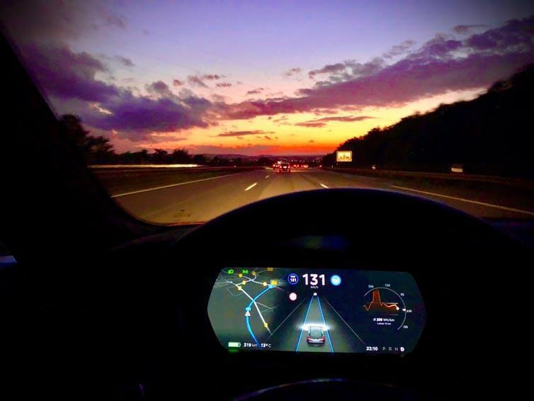The dashboard seen from inside an electric car at sunset