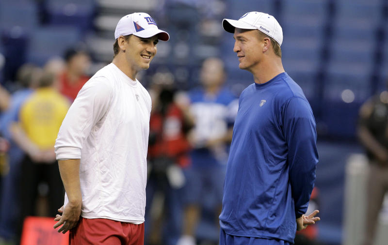 """FILE - This Sept. 19, 2010 file photo shows New York Giants quarterback Eli Manning, left, talking with his brother, Indianapolis Colts quarterback Peyton Manning, before an NFL football game in Indianapolis. Eli says he didn't want to host """"Saturday Night Live"""" after his first Super Bowl victory because it came so soon after big brother Peyton's appearance a year earlier. He sent word back to the show's executives that perhaps he'd host if he won another championship. Sure enough, the Giants quarterback said yes after his second title and will star in the comedy sketches Saturday. (AP Photo/Darron Cummings, File)"""