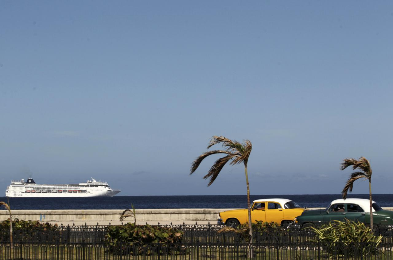 A cruise ship sails offshore as a pair of vintage American cars pass by while the country pays tribute to Cuba's late President Fidel Castro in Havana, Cuba, November 29, 2016.  REUTERS/Stringer  EDITORIAL USE ONLY. NO RESALES. NO ARCHIVE