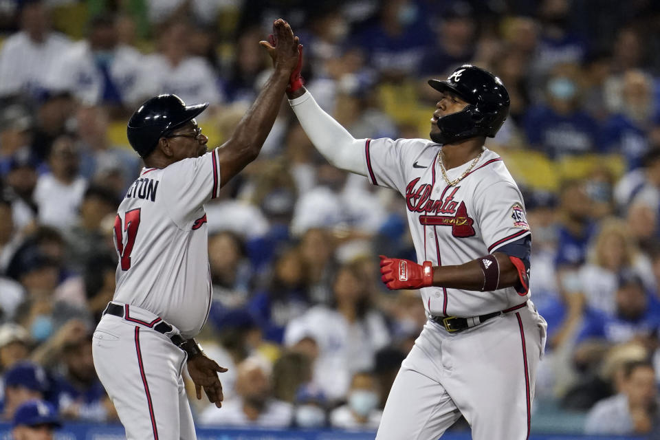 Atlanta Braves' Jorge Soler, right, celebrates his solo home run with third base coach Ron Washington during the sixth inning of a baseball game against the Los Angeles Dodgers Monday, Aug. 30, 2021, in Los Angeles. (AP Photo/Marcio Jose Sanchez)