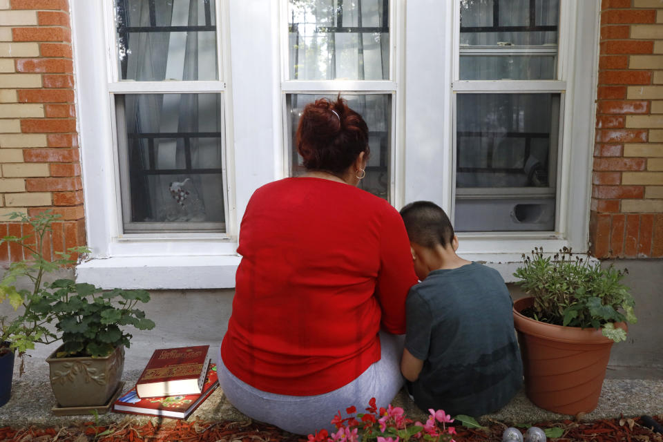 Eugenia Rodriguez shares a moment with her youngest son, Aaron, 6, while reading a children's book Friday, July 2, 2021, in Chicago's Little Village neighborhood. Rodriguez hasn't been eligible for insurance coverage after overstaying a visitor visa from Mexico. She used to wake up every two or three hours at night to check on her mother. Since getting health insurance through the Illinois program, her mother has all the medications she needs. (AP Photo/Shafkat Anowar)