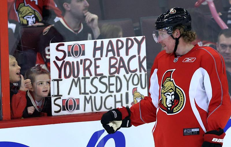 FILE - In a Sunday, Jan. 13, 2013 file photo, Ottawa Senators team captain Daniel Alfredsson acknowledges two young fans who show their appreciation for his team coming back after the NHL hockey lockout ended at training camp in Ottawa, Ontario. The lockout that lasted 119 days has ended, the new collective bargaining agreement is in place and the NHL is finally about to play games again after hastily arranged week-long training camps around the league. (AP Photo/The Canadian Press, Fred Chartrand, File)