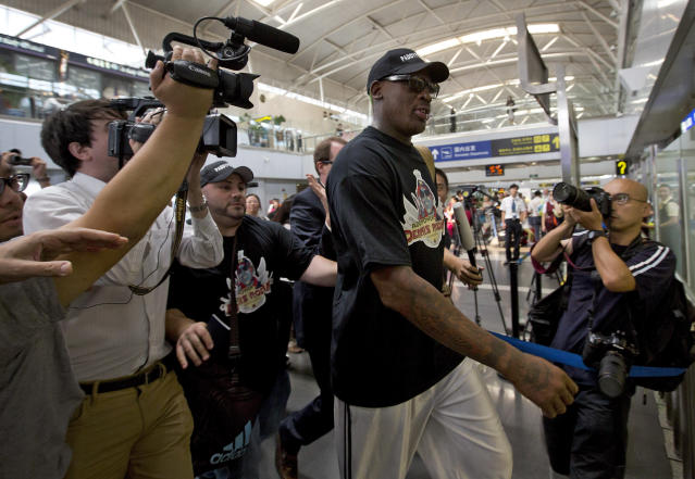 Former NBA star Dennis Rodman, center, is surrounded by media as he arrives at the departure hall of Beijing International Capital Airport in Beijing Tuesday, Sept. 3, 2013. Rodman is heading to North Korea for the second time this year for what he says is a friendly visit to his friend, the communist nation's leader, Kim Jong Un. (AP Photo/Andy Wong)