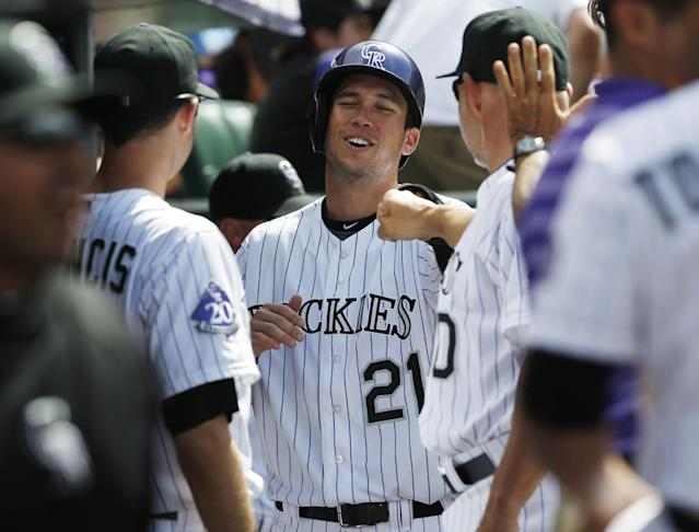 Colorado Rockies' Tyler Colvin, center, is congratulated by teammate Jeff Francis, left, and coach Dante Bichette after scoring on an RBI-single by Tyler Chatwood against the Philadelphia Phillies in the fourth inning of a baseball game in Denver, Saturday, June 15, 2013. (AP Photo/David Zalubowski)