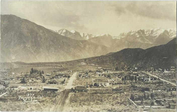 Snow capped mountains rise behind Tujunga in this vintage postcard
