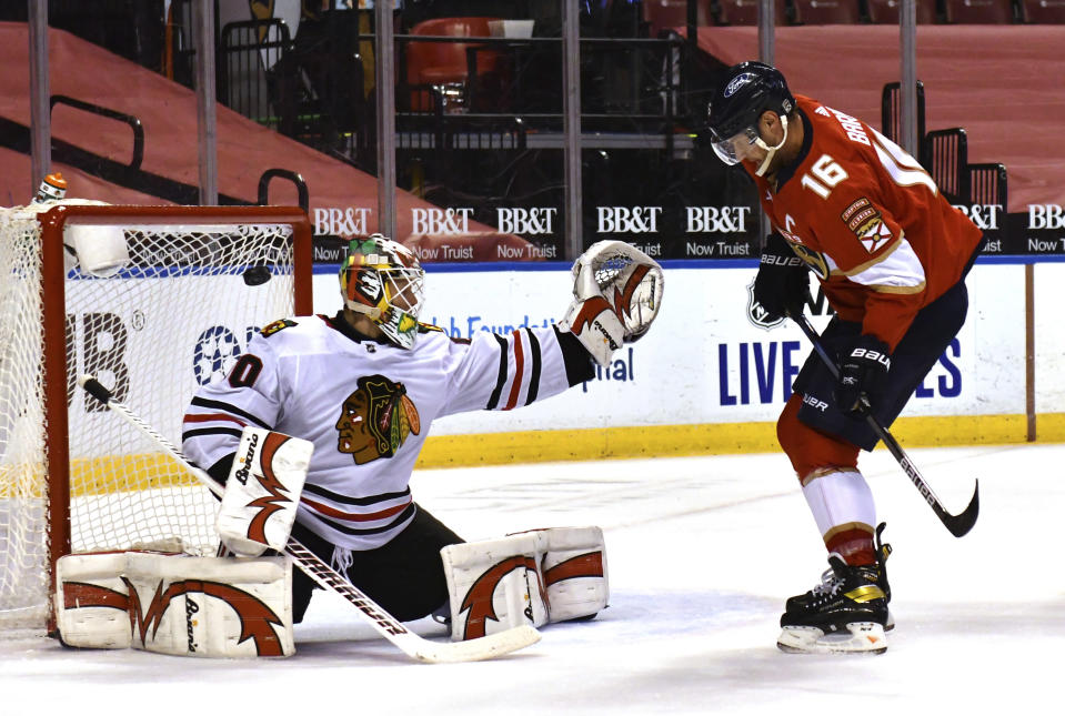 Chicago Blackhawks goaltender Collin Delia (60) knocks the puck over the goal as Florida Panthers center Aleksander Barkov (16) looks on during the second period of an NHL hockey game Sunday, Jan. 17, 2021, in Sunrise, Fla. (AP Photo/Jim Rassol)
