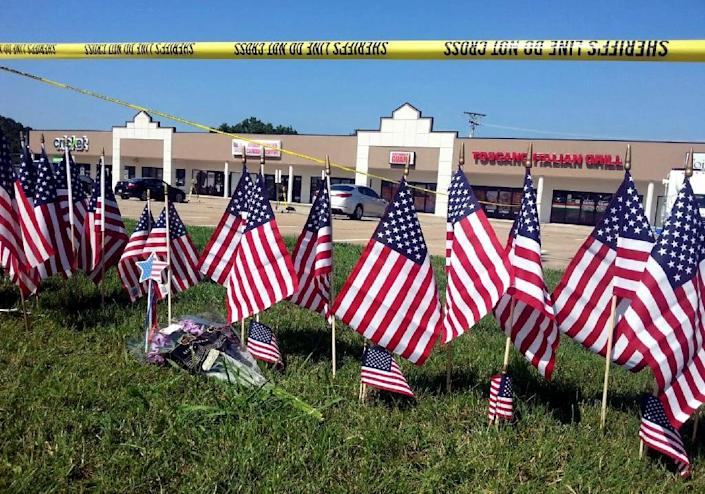 Flags and flowers are placed at a memorial site near the Armed Forces Career Center in Chattanooga, Tennesse, on July 17, 2015 following a gun attack that killed five service members (AFP Photo/Edn Woldearegay)