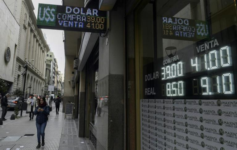 Pedestrians walk by a Buenos Aires exchange bureau where the buy-sell board displays the Argentine peso exchange values