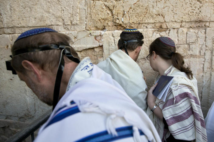 FILE - In this Thursday, Feb. 25, 2016 file photo, American and Israeli Reform rabbis pray at the Western Wall, the holiest site where Jews can pray in Jerusalem's old city. Israel's recent detentions of Jewish-American critics entering the country is shining a spotlight on a growing gulf between the country's hard-line government and the predominantly liberal Jewish community in the U.S. (AP Photo/Sebastian Scheiner, File)
