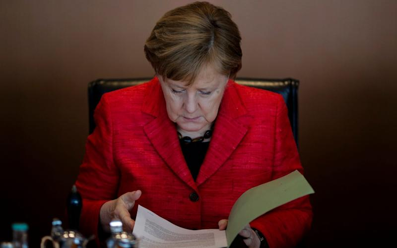 German Chancellor Angela Merkel reads a document as she attends the weekly cabinet meeting of the German government at the chancellery in Berlin