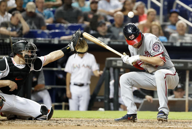 Washington Nationals' Trea Turner is hit by a pitch as Miami Marlins catcher J.T. Realmuto looks on during the sixth inning of a baseball game, Tuesday, Sept. 18, 2018, in Miami. (AP Photo/Wilfredo Lee)