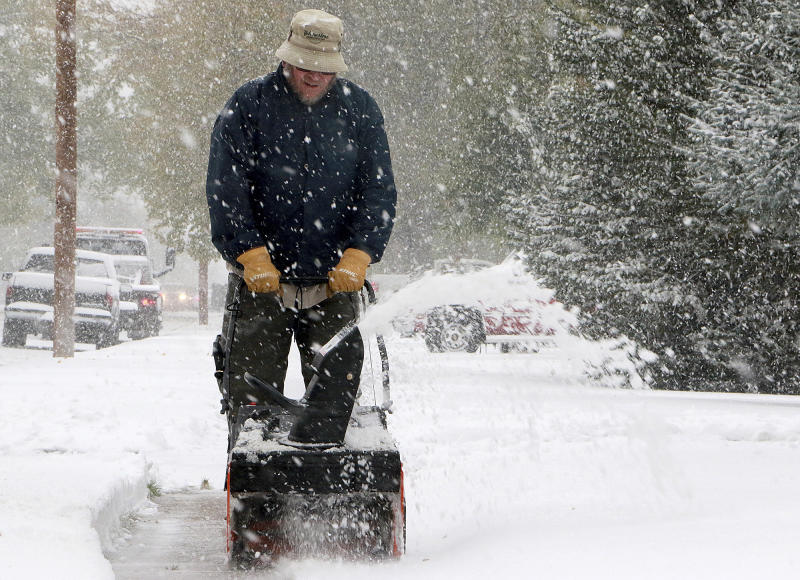 Kevin Hill uses a snow blower to remove snow from his front sidewalk as snow continues to fall Thursday, Oct. 10, 2019, in Scottsbluff, Neb. The Panhandle saw its first snow of the season Wednesday night into Thursday. (Lauren Brant/The Star-Herald via AP)