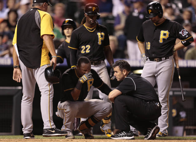 PIttsburgh Pirates players watch as medical staff examine Pirates batter Starling Marte's left hand after he was hit by a pitch from Colorado Rockies pitcher Josh Outman in the seventh inning of a baseball game in Denver on Saturday, Aug. 10, 2013. Colorado beat Pittsburgh 6-4.(AP Photo/Joe Mahoney)
