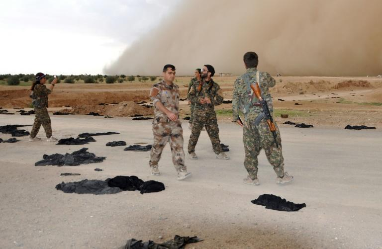 Fighters from the Syrian Democratic Forces (SDF) walk along a road dotted with black veils ditched by women after they crossed over from Islamic State group territory near Tishreen Farms, on the northern outskirts of Raqa on May 2, 2017
