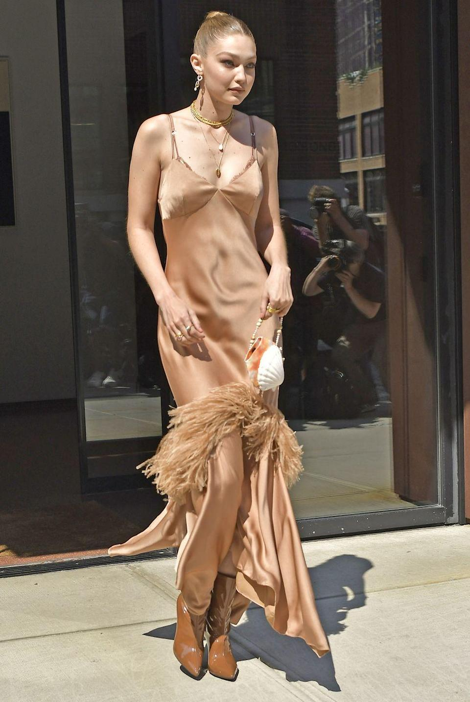 <p>In a champagne fringe slip dress, tan boots, layered gold necklaces, and a shell handbag. </p>