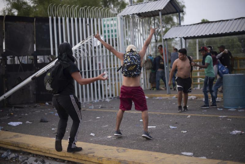 A Central American migrant taunts Mexican authorities at a border bridge crossing connecting Guatemala and Mexico, in Tecun Uman, Guatemala, Sunday, Oct. 28, 2018. A new group of migrants, who called themselves a second caravan, gathered on a bridge after forcing their way through a gate at the Guatemalan end. (AP Photo/Santiago Billy)
