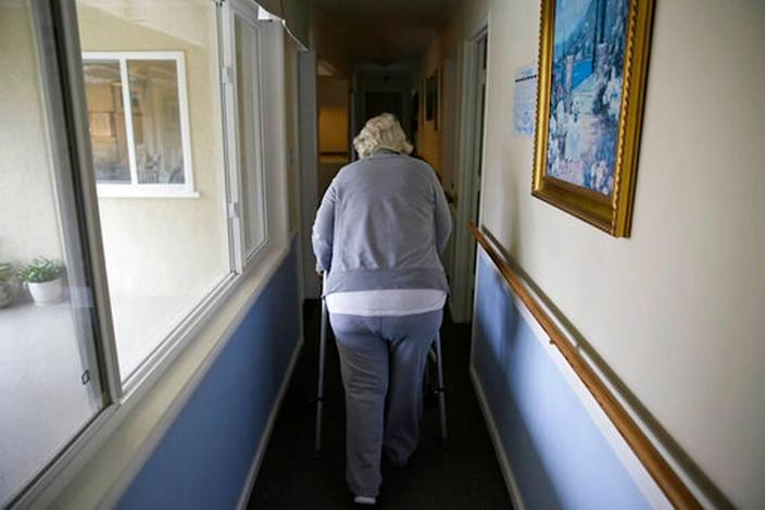 FILE - In this Dec. 5, 2019, file photo, a woman walks to her room at a senior care home in Calistoga, Calif.