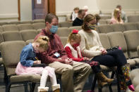 Jonathan Vaughn, second from left, and his family, Addison, 5, left, Ann Marie, 7, second from right, and wife Alesha Vaughn pray during services in the Worship Center at Highland Colony Baptist Church in Ridgeland, Miss., Nov. 29, 2020. The church practices covid protocols by allowing families to sit spaced out from others, separating older and more vulnerable members in the worship hall and providing sanitizer and masks at the entrance. (AP Photo/Rogelio V. Solis)