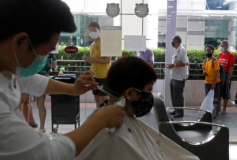 Customers queue up to have their haircut outside a hairdressing salon as they reopen for business amid the outbreak here on 12 May, 2020. (PHOTO: Reuters)