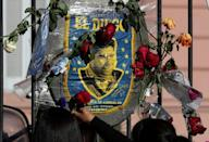 Fans of late Argentinian football legend Diego Maradona put flowers on an image of the football player outside the presidential palace in Buenos Aires, on November 26, 2020