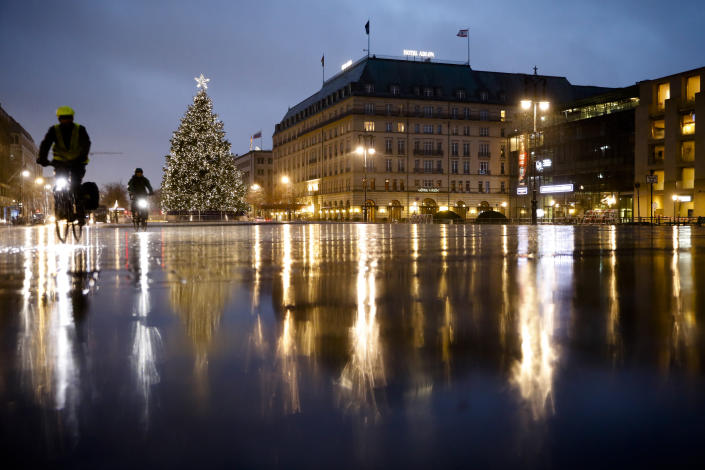 Rain covers the deserted Pariser Platz at the Brandenburg Gate in Berlin, Germany, Tuesday, Dec. 22, 2020. The Robert Koch Institute, Germany's national disease control agency, figures for Germany: 19,528 new cases, a week ago it was14,432 and another 731 deaths. (AP Photo/Markus Schreiber)