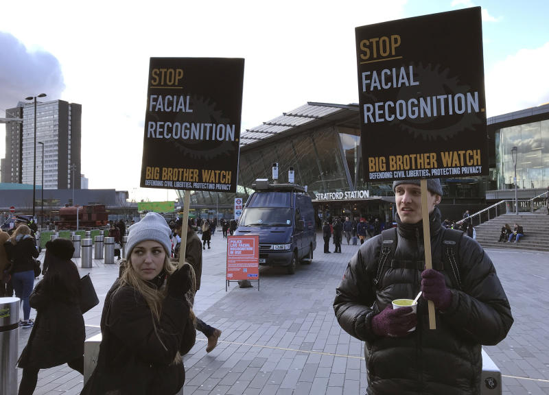 "Rights campaigner Silkie Carlo, left, demonstrates in front of a mobile police facial recognition facility outside a shopping centre in London Tuesday Feb. 11, 2020, ""We don't accept this. This isn't what you do in a democracy,"" said Carlo, director of privacy campaign group Big Brother Watch. London police started using facial recognition surveillance cameras mounted on a blue police van on Tuesday to automatically scan for wanted people, as authorities adopt the controversial technology that has raised concerns about increased surveillance and erosion of privacy. (AP Photo/Kelvin Chan)"
