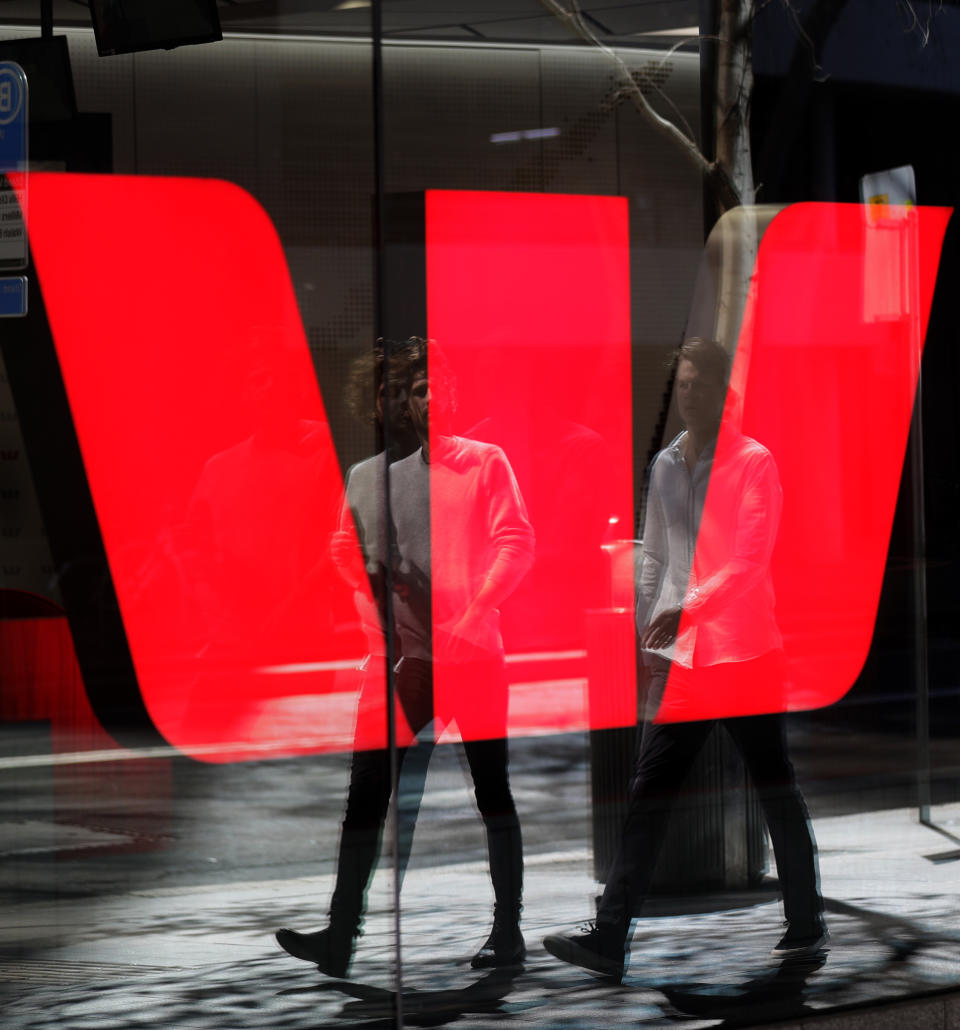 Two men are reflected in a window as they walk past a Westpac bank branch in Sydney, Thursday, Sept. 24, 2020. Westpac, Australia's second-largest bank, agreed to pay a 1.3 billion Australian dollar ($919 million) fine for breaches of anti-money laundering and counterterrorism financing laws, the largest ever civil penalty in Australia, a financial crime regulator said. (AP Photo/Rick Rycroft)