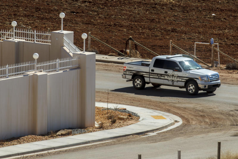 FILE - In this Feb. 18, 2013, file photo, a Marshal with the FLDS Hildale/Colorado City Town Marshals patrols along the walls of a compound built for imprisoned leader Warren Jeffs in Hildale, Utah. The federal government's bid to dismantle the police department in a polygamous community on the Arizona-Utah border has been rejected by a judge as too drastic and expensive. But the towns will still be under court supervision for the next decade as punishment in a religious discrimination case. (Trent Nelson/Salt Lake Tribune via AP, File)