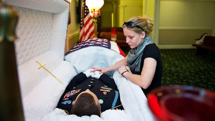 """<div class=""""inline-image__caption""""><p>""""Seana Arrechaga holds her husband's hands as he lays in his casket Wednesday, April 6, 2011 in Clarksville, TN. SFC Ofren Arrechaga was killed in a firefight in Afghanistan eight days earlier.""""</p></div> <div class=""""inline-image__credit"""">Katherine Frey/The Washington Post via Getty Images</div>"""