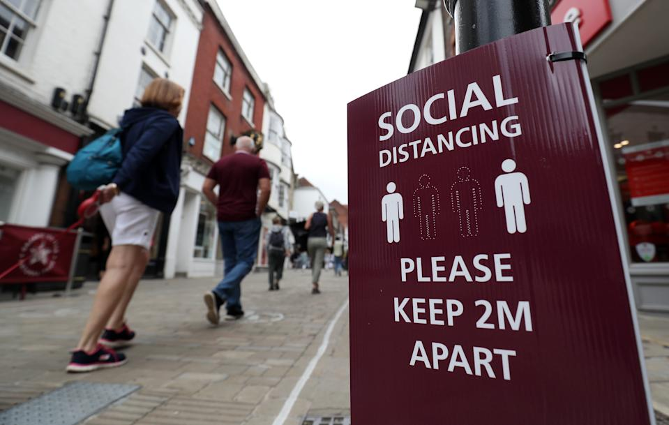 People make their way past a social distancing sign on the High street in Winchester, Hampshire, after the lifting of further coronavirus lockdown restrictions in England. (Photo by Andrew Matthews/PA Images via Getty Images)