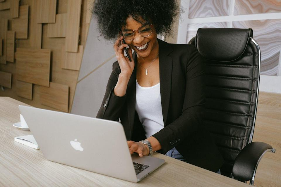 A young woman sits on the phone in front of an open laptop laughing.
