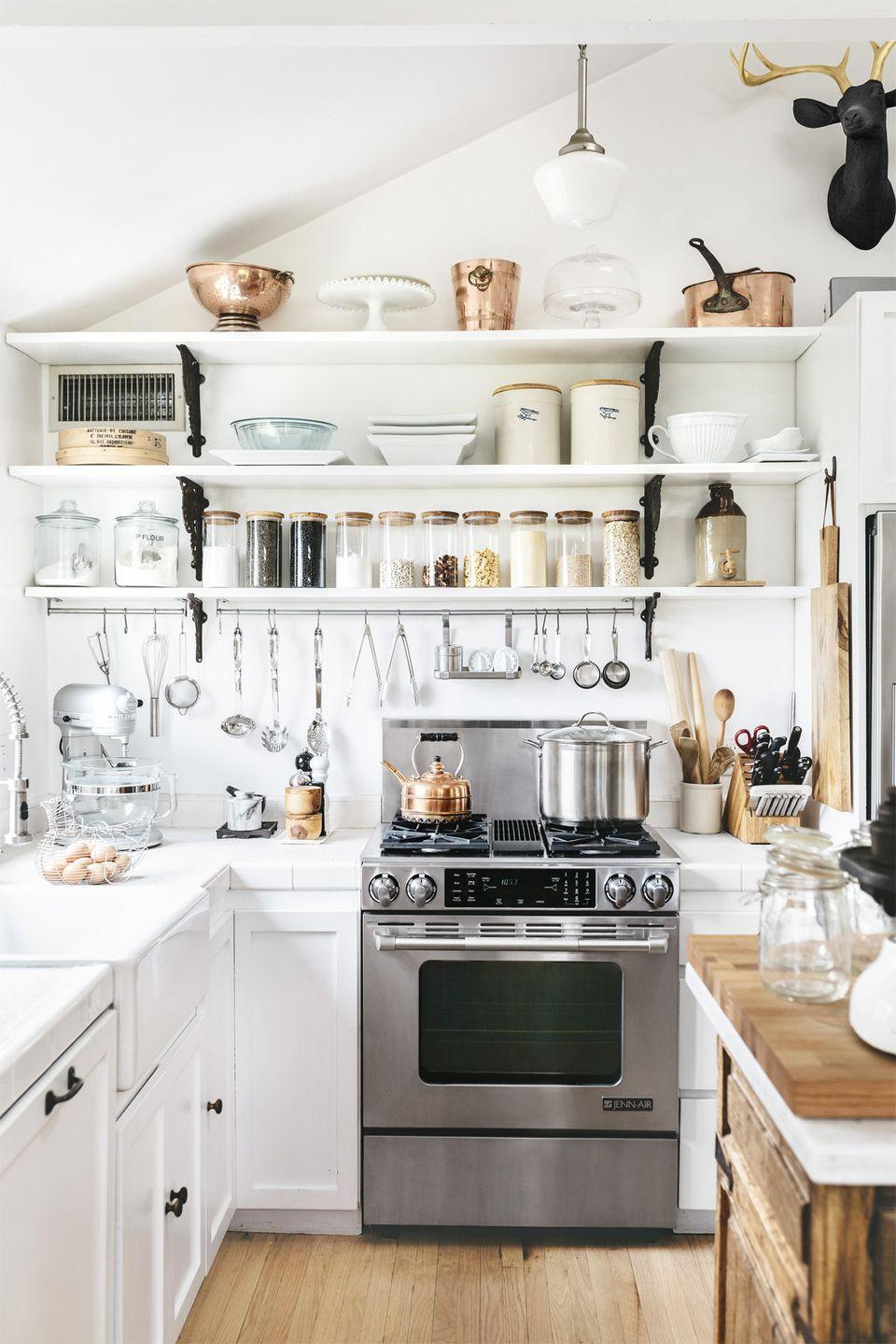 """<p>This economical alternative to upper cabinetry keeps everything within sight and reach. Plus, <a href=""""https://www.countryliving.com/home-design/decorating-ideas/g4705/farmhouse-staples/"""" rel=""""nofollow noopener"""" target=""""_blank"""" data-ylk=""""slk:the farmhouse staple"""" class=""""link rapid-noclick-resp"""">the farmhouse staple</a> provides the perfect excuse to buy beautiful kitchen items in <a href=""""https://www.amazon.com/s/ref=nb_sb_ss_c_1_17?url=search-alias%3Daps&field-keywords=rose+gold+kitchen+accessories&tag=syn-yahoo-20&ascsubtag=%5Bartid%7C10050.g.1293%5Bsrc%7Cyahoo-us"""" rel=""""nofollow noopener"""" target=""""_blank"""" data-ylk=""""slk:rose gold"""" class=""""link rapid-noclick-resp"""">rose gold</a> or other stunning materials and colors.</p>"""