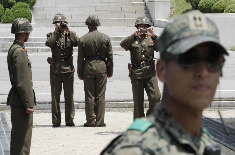 North Korean soldiers take pictures as a South Korean army soldier, right, stands guard after a ceremony marking the 59th anniversary of the signing of the armistice agreement that ended the Korean War on July 27, 1953, at the border villages of Panmunjom, South Korea, Friday, July 27, 2012. (AP Photo/Ahn Young-joon. Pool)